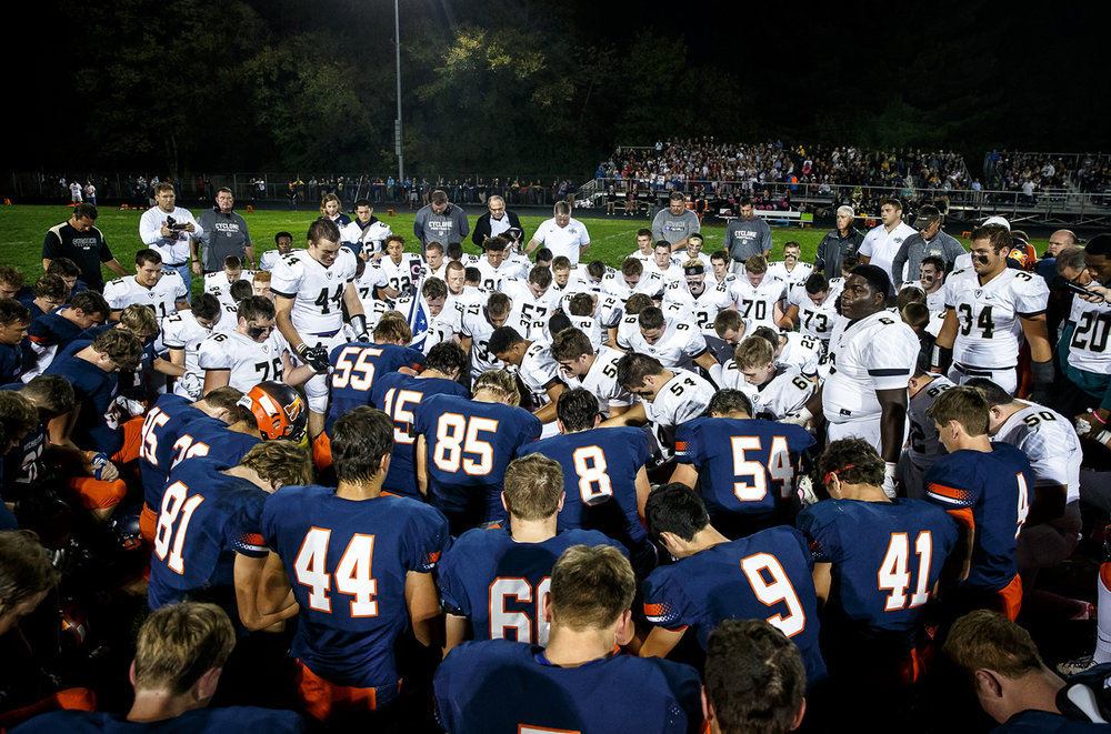 Sacred Heart-Griffin's John Keen (44) leads a prayer with the Cyclones and the Rochester Rockets for Liz Leonard, the mother Rochester's Derek Leonard and the wife of Sacred Heart-Griffin's Ken Leonard prior to kickoff at Rocket Booster Stadium, Friday, Oct. 6, 2017, in Rochester, Ill. [Justin L. Fowler/The State Journal-Register]
