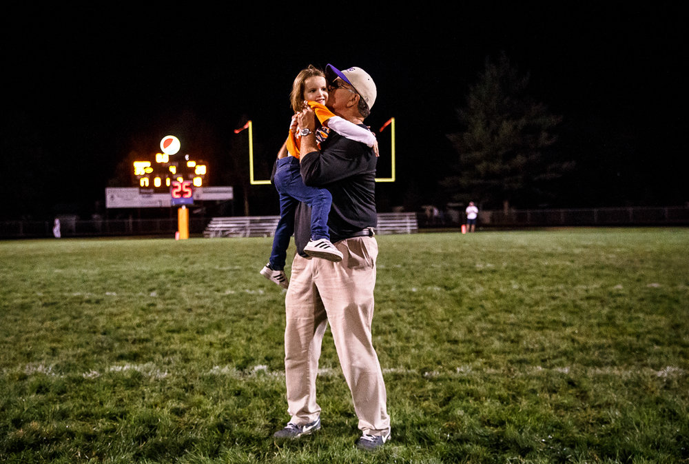 Sacred Heart-Griffin head football coach Ken Leonard gets a hug from his granddaughter, Julia Leonard, after the Cyclones were defeated 35-28 by Rochester at Rocket Booster Stadium, Friday, Oct. 6, 2017, in Rochester, Ill. [Justin L. Fowler/The State Journal-Register]