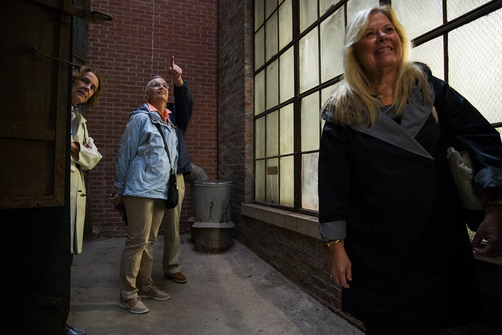 Sarah Bunn, left, Peggy Ryder and Karen Giannone investigate the light well between the two sections of the old Schnepp and Barnes building during a tour of the construction of Springfield's Kidzeum of Health and Science Friday, Oct. 6, 2017. The lightwell allows natural light to flood the deep interior spaces of the building through large windows. [Ted Schurter/The State Journal-Register]