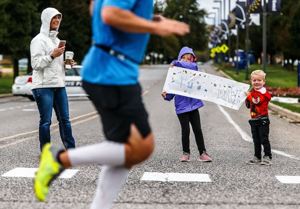Addison Nikson, 8, holds up a sign of encouragement with her brother, Luke Nikson, 3 as they cheer on their dad, Jason Nikson, along with their mother Patty Nikson, left, as he finishes the first lap during the 5th annual Springfield Clinic Springfield Marathon at the University of Illinois Springfield, Sunday, Oct. 15, 2017, in Springfield, Ill. The event includes distances of 3/4 marathon, half marathon, quarter marathon and a marathon relay. [Justin L. Fowler/The State Journal-Register]