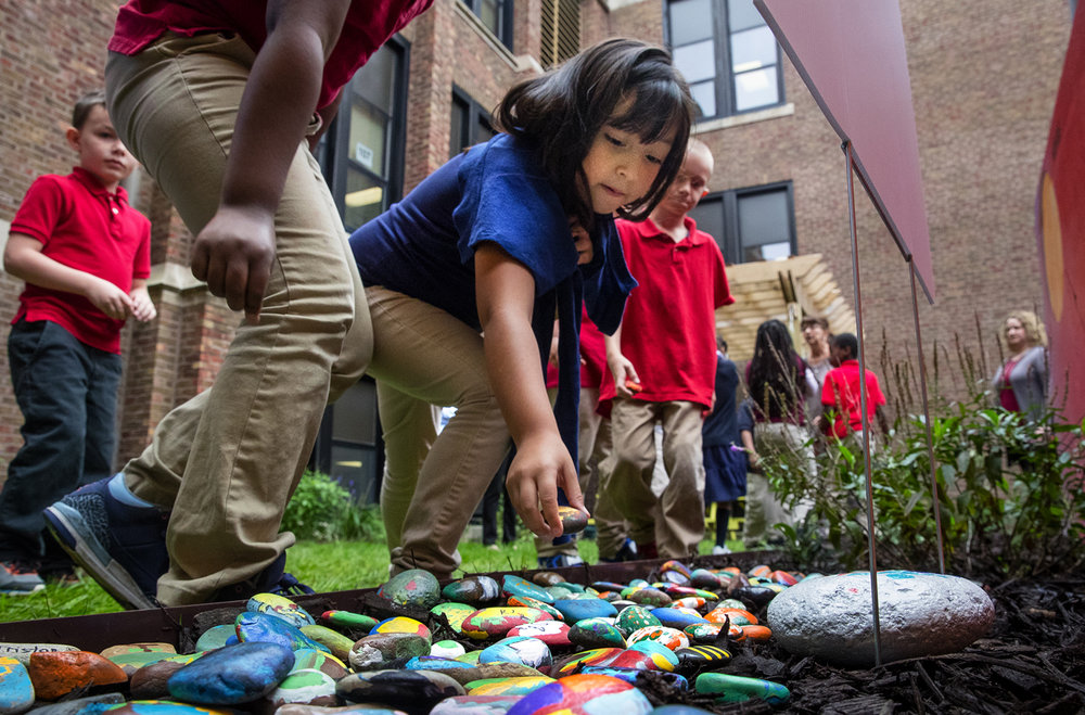 "Lilyanna Lopez places her painted rock into the courtyard at Feitshans Elementary Thursday, Oct. 12, 2017. Students painted their own rocks while listening to the story ""Only One You,"" a story about individuality and treating people with kindness written by Linda Kranz. The school will continue to add to the hundreds of rocks placed today during their ongoing effort to teach kindness. [Ted Schurter/The State Journal-Register]"