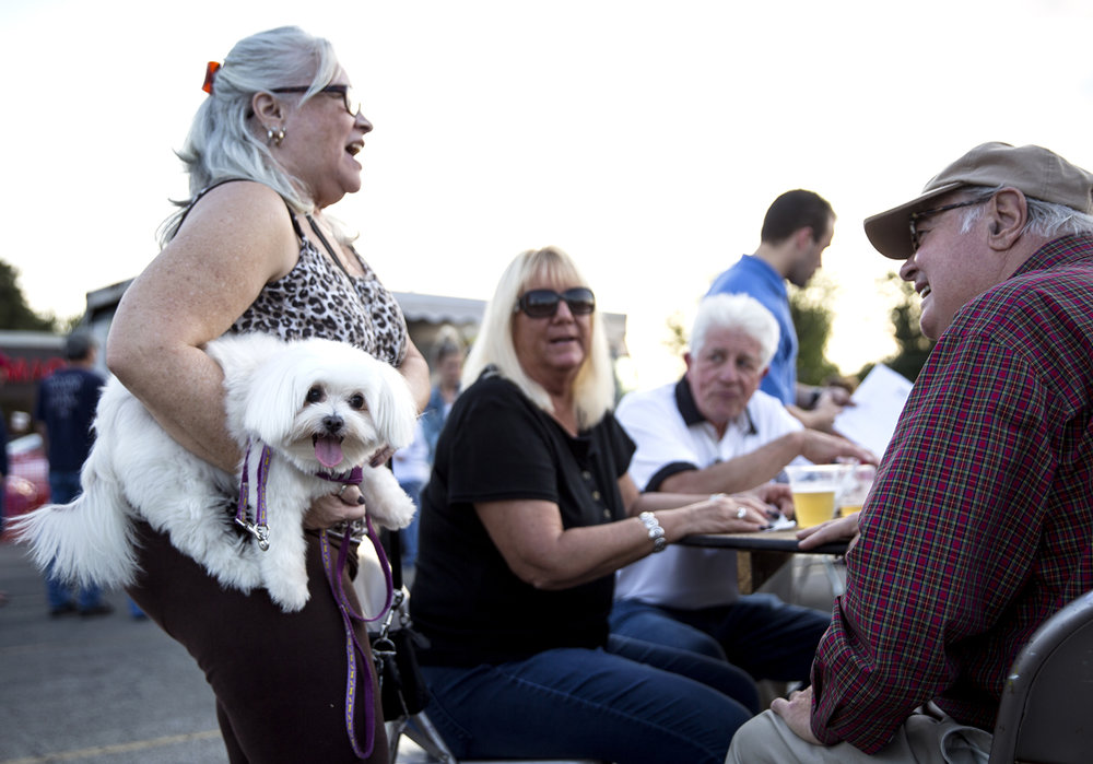 Maggie Woods visits with friends, Deirdre Caruso, her husband, Tony, and Tony Leone, right, while her dog Bella keeps an eye on a bystander at Appetite on the Avenue, a food truck meet-up in the parking lot of Shop 'n Save on North Grand Avenue Monday, Oct. 9, 2017. The event was  sponsored by the North Grand Avenue Improvement Association and co-hosted by the Enos Park Neighborhood Association. [Rich Saal/The State Journal-Register]