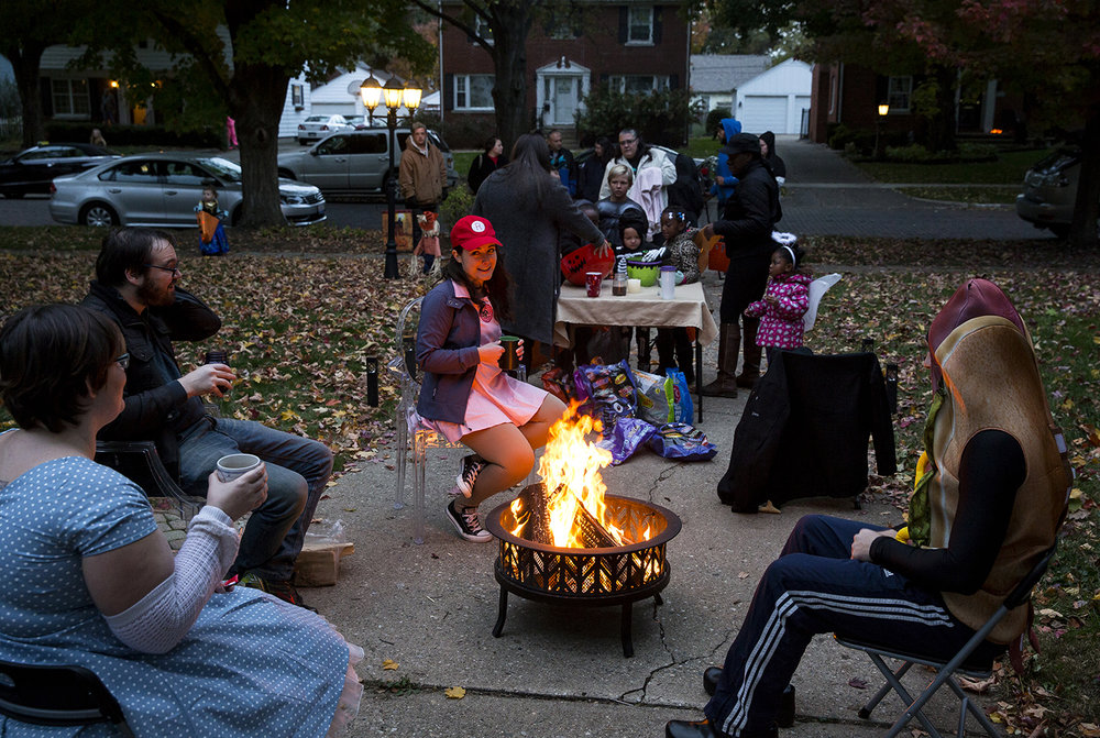 Victoria and Adam Lipson, left, and Lauren and Dave McNamara warm themselves by a fire during Halloween festivities on South Glenwood Avenue Tuesday, Oct. 31, 2017. [Rich Saal/The State Journal-Register]