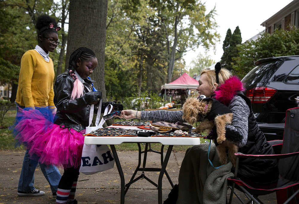 Heidi Voegele hands a treat to Leah Swope, who was trick or treating with Ashanti Hatchett Tuesday, Oct. 31, 2017 on South Glenwood Avenue. [Rich Saal/The State Journal-Register]