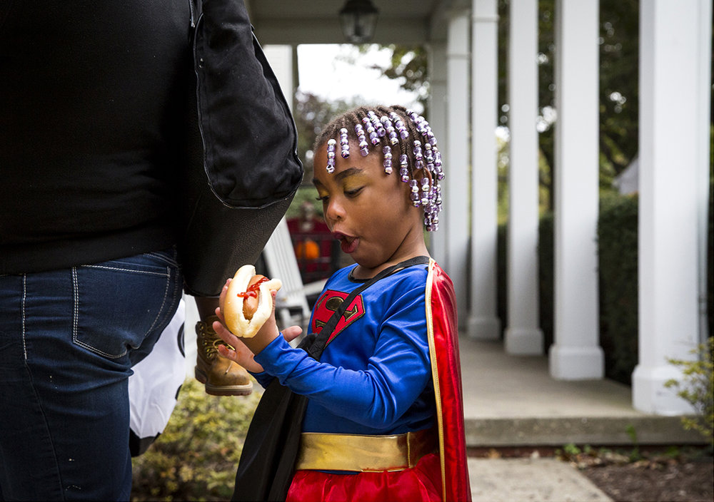 Anyla Nathan munches on a hot dog she was given while trick or treating on South Glenwood Avenue Tuesday, Oct. 31, 2017. [Rich Saal/The State Journal-Register]