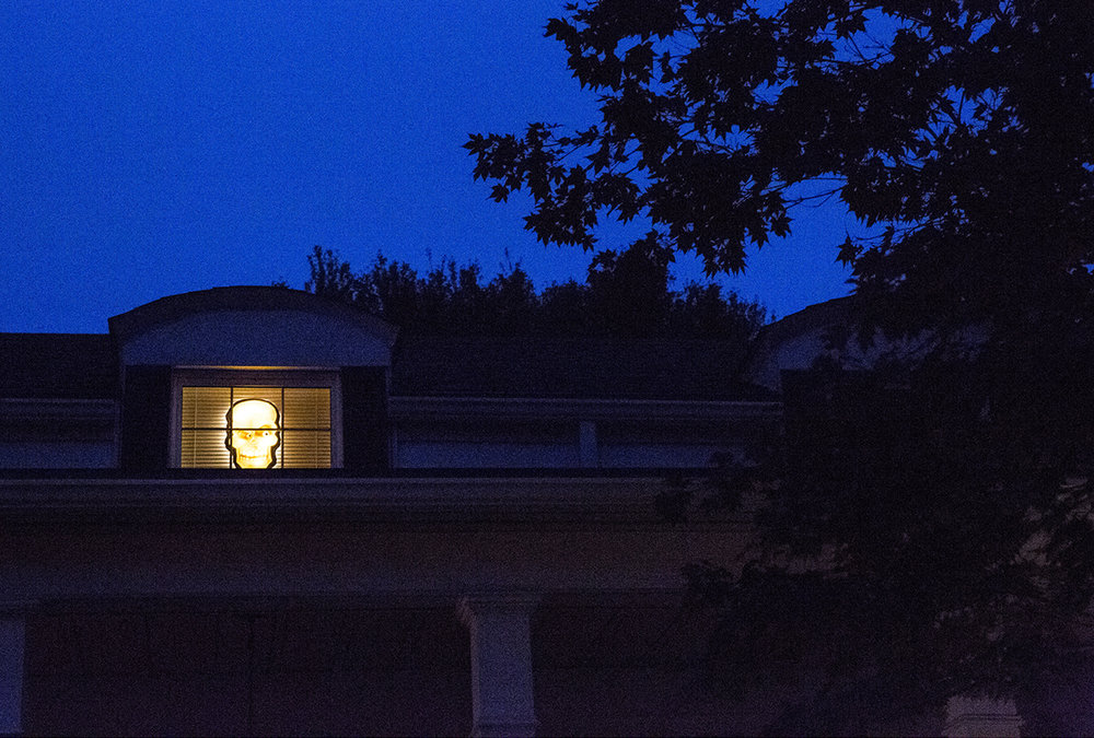 An illuminated Halloween mask peers out of a window in a house on South Glenwood Avenue Tuesday, Oct. 31, 2017. [Rich Saal/The State Journal-Register]