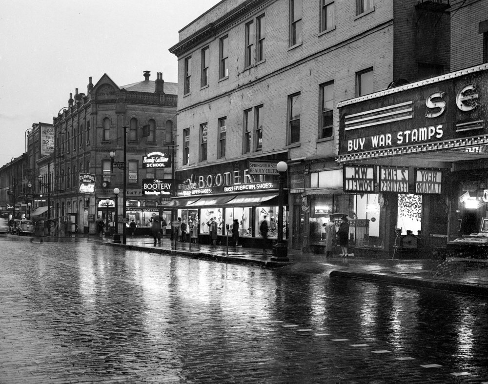 Downtown Springfield, corner of Monroe and Fifth streets, November 9, 1942. File/The State Journal-Registerpicpast; spihistory; weather; rain; streets; retail; downtown; theater; Claypool Drugs; Senate Theater; BooteryPublished as Picturing the Past Nov. 5, 2017The heavy clouds that moved in with a thunderstorm on a Monday in early November cast such a dark pall over the city that at 9 a.m., it looked like dusk. Light from The Bootery shoe shop and Claypool Drugs  are reflected off the wet bricks on Monroe Street and people waiting for their bus take shelter under awnings, or carry umbrellas. The scene could have been on the same block as the diner in Edward Hopper's painting, Nighthawks, coincidently painted the same year.  The image was shot for a short story reporting that more than an inch and a half of rain had fallen, but that the 70 degree temperature would give way to colder and blustery weather the next day. [File/The State Journal-Register]