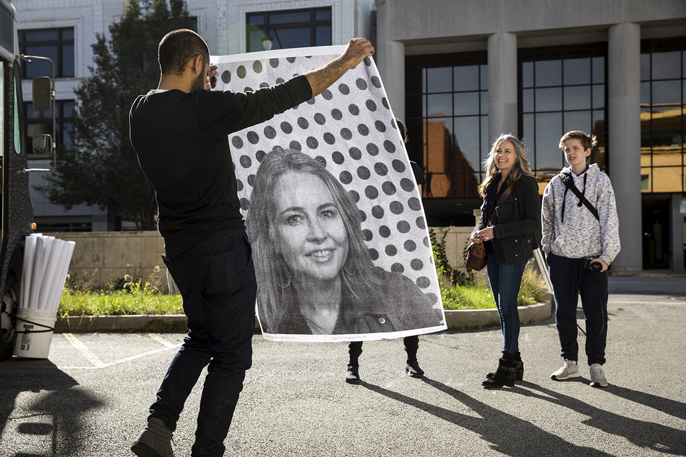 Babak Housh with the Inside Out Project holds the portrait of Carrie Beard that had just been made in a camera truck Thursday, Oct. 26, 2017 in a parking lot between the Kerasotes Building and FrankieÕs Brewhaus on Washington Street. Beard and her son, Gus, right, were part of a public art initiative to create a portrait of diverse Americans who support Dreamers, or recipients of the federal governmentÕs DACA program. The poster-size pictures were mounted on the wall of the Kerasotes building and are designed to last up to three months. [Rich Saal/The State Journal-Register]