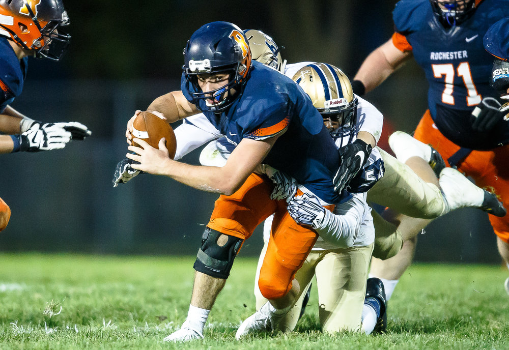 Rochester quarterback Nic Baker (8) battles for extra yards on a rush while being dragged down by Belleville Althoff's Anthony Hughes (54) in the first half during the second round of the IHSA Class 4A Playoffs at Rocket Booster Stadium, Saturday, Nov. 4, 2017, in Rochester, Ill. [Justin L. Fowler/The State Journal-Register]
