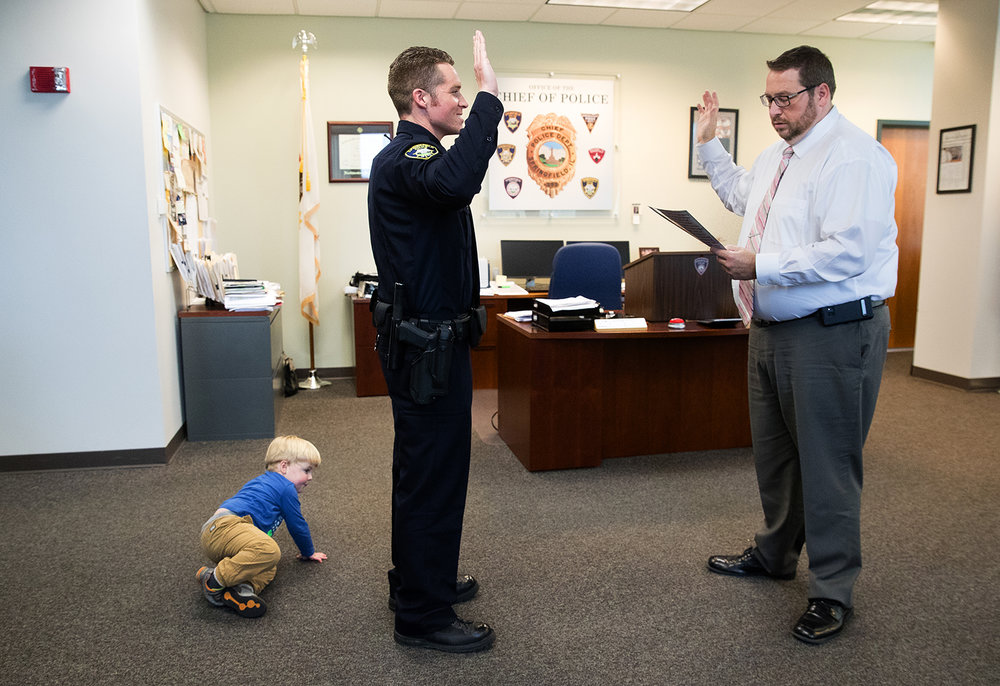 Springfield Police Officer Josh Friedman's son Saxon crawls on the floor in search of his toy as he takes his oath from Chief Kenny Winslow during a ceremony in the chief's office Thursday, Nov. 2, 2017. [Ted Schurter/The State Journal-Register]