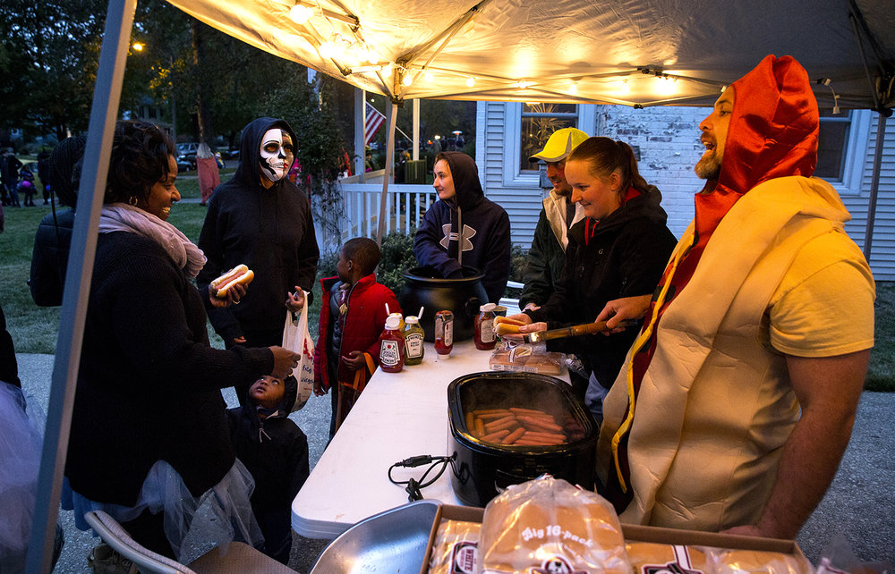 Quinton Mitchell prepared 600 hot dogs and gave them away to trick or treaters who came to his home in the 2100 block of S. Glenwood Avenue Tuesday, Oct. 31, 2017. He had help from Morgan Throop, center, her dad Earl Throop, Jr. and Maddy Hickey. The neighborhood has seen up to 800 trick or treaters on Halloween, and it's known to make them feel welcome. [Rich Saal/The State Journal-Register]