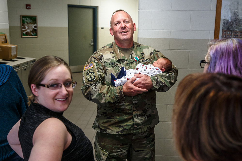 Lt. Col. Ronald Bonesz, center, holds his seven-day-old son, Logan, along with his wife, Blair, left, after a deployment ceremony for the Bilateral Embedded Staff Team (BEST) A20 at Camp Lincoln, Thursday, Nov. 9, 2017, in Springfield, Ill. Lt. Col. Bonesz, a Normal resident who served two tours in Iraq, will be leaving his wife, newborn son and his 16-year-old daughter for a seven to nine-month deployment to lead a six-man Illinois National Guard team that will be embedded with Polish forces in Afghanistan. [Justin L. Fowler/The State Journal-Register]