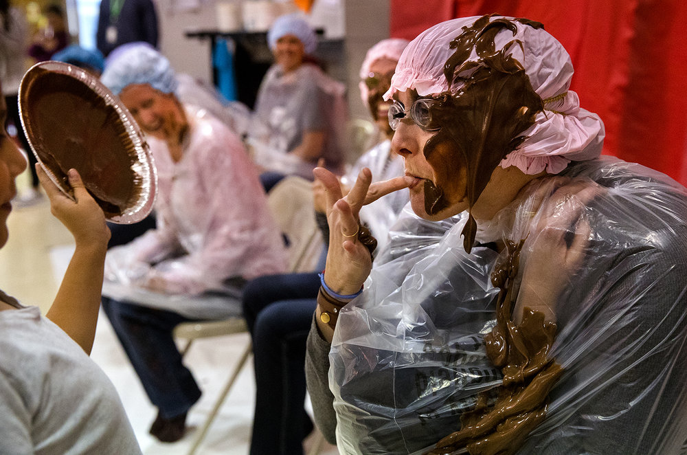 "Leslie Poppenhouse samples a bit of the ""Marsh Mud Pie"" that was poured over her head by Angel Rivera during a fundraiser at Owen Marsh Elementary for the local United Way Thursday, Nov. 9, 2017. Students' names were entered into a drawing each time they purchased a $2 ticket that earned them a chance to be drawn for the pie throwing duty. [Ted Schurter/The State Journal-Register]"