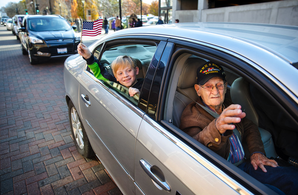 World War II veteran Biagio Rusciolelli's and his grandson Noah Stuemke wave to the crowd gathered for the Veteran's Day parade along Capitol Avenue Saturday, Nov. 11, 2017. Area WWII veterans served as grand marshals for the parade. [Ted Schurter/The State Journal-Register]