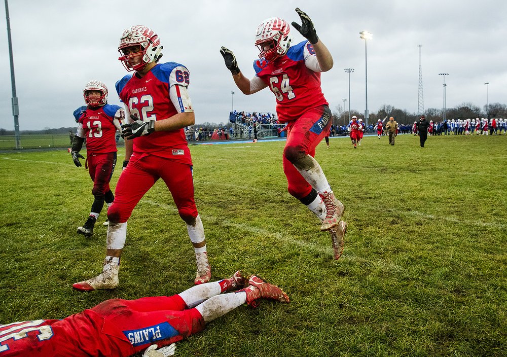 Pleasant Plains' Carter Weiters pounces on teammate Colby McBride as they celebrate their win against Anna-Jonesboro during the IHSA Class 3A football semifinal game at Pleasant Plains High School Saturday, Nov. 18, 2017. [Ted Schurter/The State Journal-Register]
