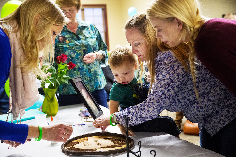 Karen Wetzstein pinches a fingerful of material to sprinkle on a floragraph of John Lefferts, her nephew who died of an aneurysm in 2004, during an event in Sherman Sunday, Nov. 12, 2017. Wetzstein was joined by her daughter Lauren and her son Brantley. Lefferts' sister, Eleanor, is at left. The floragraph will be incorporated into the Donate Life Rose Bowl Parade float.[Ted Schurter/The State Journal-Register]