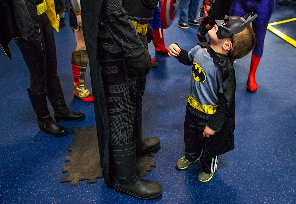 "Four-year-old Hollis Lewis gazes up at Batman, portrayed by Nathan Paulus with the group Superheroes Saving Smiles during Superhero Night at The Nelson Center as the Springfield Jr. Blues faced Coulee Region Chill Friday, Nov. 17, 2017. The superheros mingled with the crowd during the event that also featured themed giveaways including tickets to the new ""Justice League"" movie. [Ted Schurter/The State Journal-Register]"