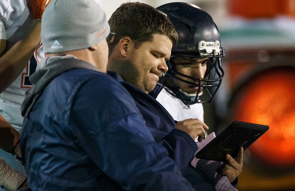 Rochester head football coach Derek Leonard reviews game footage with Rochester quarterback Nic Baker (8) on the sidelines as the Rockets take on Morris in the fourth quarter during the IHSA Class 4A State Championship at Huskie Stadium, Friday, Nov. 24, 2017, in Dekalb, Ill. [Justin L. Fowler/The State Journal-Register]