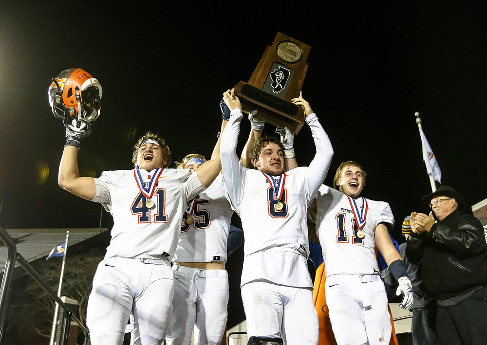 Rochester's Nick Capriotti (41) Rochester's Mike McNicholas (85) Rochester quarterback Nic Baker (8) and Rochester's Skylor Caruso (11) hoist up the championship trophy after defeating Morris 24-21 in the IHSA Class 4A State Championship at Huskie Stadium, Friday, Nov. 24, 2017, in Dekalb, Ill. [Justin L. Fowler/The State Journal-Register]