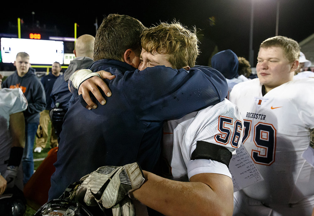 Rochester's Clayton Blanshan (56) gets a hug from Rochester head football coach Derek Leonard after the Rockets defeated Morris 24-21 in the IHSA Class 4A State Championship at Huskie Stadium, Friday, Nov. 24, 2017, in Dekalb, Ill. [Justin L. Fowler/The State Journal-Register]