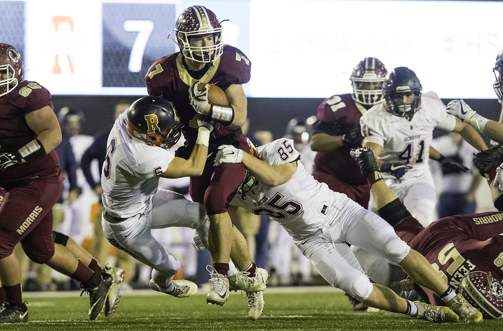 Morris' Kameron Dransfeldt plows into Rochester's Cade Eddington and Mike McNicholas during the IHSA Class 4A championship game at Huskie Stadium in Dekalb, Ill., Friday, Nov. 24, 2017. [Ted Schurter/The State Journal-Register]