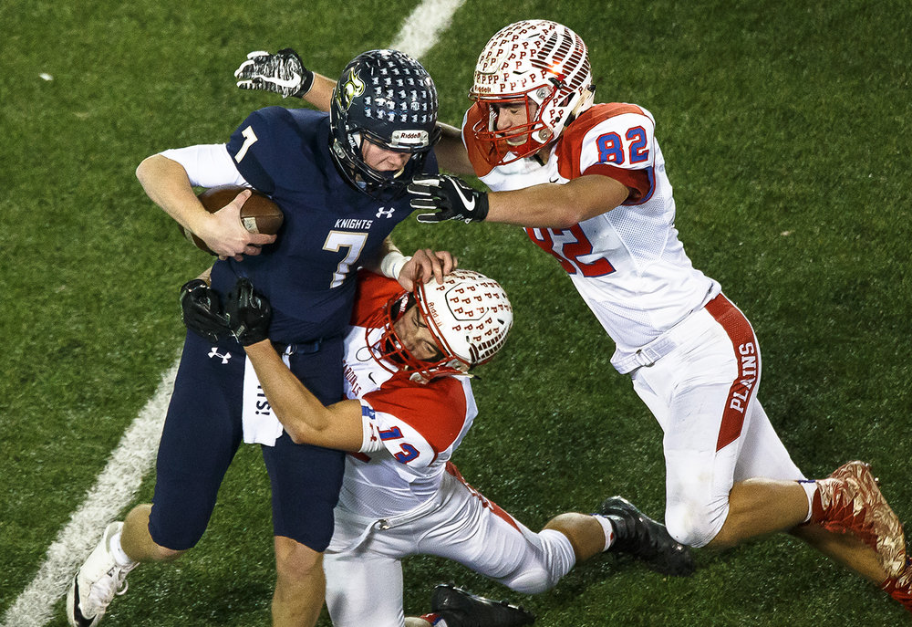 Pleasant Plains' Lucas Western (13) and Pleasant Plains' Tristen Tewes (82) brings down Elmhurst IC Catholic quarterback CJ West (7) for a sack and a loss of yardage in the second quarter during the IHSA Class 3A State Championship at Huskie Stadium, Friday, Nov. 24, 2017, in Dekalb, Ill. [Justin L. Fowler/The State Journal-Register]