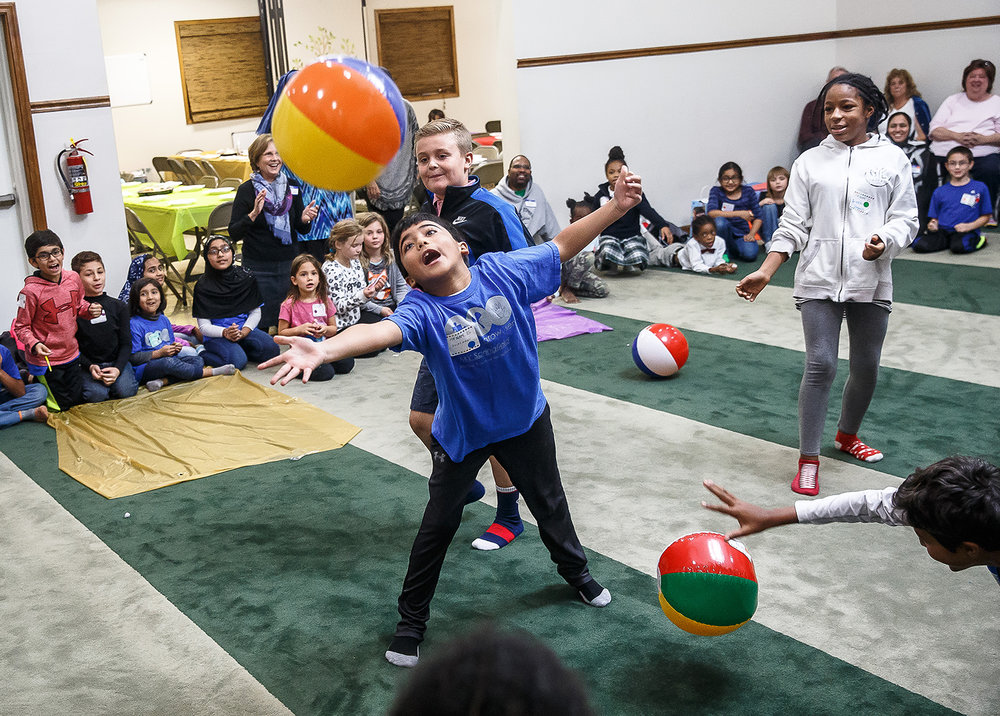 "Sulaymaan Mahmood, 8, does his best to keep a beach ball in the air as he plays a ""Minute to Win It"" game with a group of children during the Children of Abraham program at the Islamic Society of Greater Springfield mosque, Wednesday, Nov. 15, 2017, in Springfield, Ill. The program brings together kids from different faiths to build bridges and friendships through playing games and activities. [Justin L. Fowler/The State Journal-Register]"