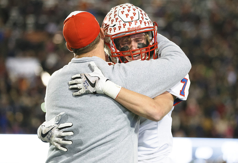 Pleasant Plains' Kai Carlberg (7) hugs Pleasant Plains head football coach Brody Walworth after the Cardinals were defeated by Elmhurst IC Catholic 35-0 in the IHSA Class 3A State Championship at Huskie Stadium, Friday, Nov. 24, 2017, in Dekalb, Ill. [Justin L. Fowler/The State Journal-Register]