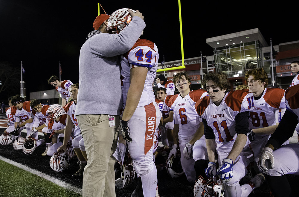 Pleasant Plains head coach Brody Walworthp hugs Nik Samson as the team gathers after their loss to IC Catholic during the IHSA Class 3A championship game at Huskie Stadium in Dekalb, Ill., Friday, Nov. 24, 2017.   [Ted Schurter/The State Journal-Register]