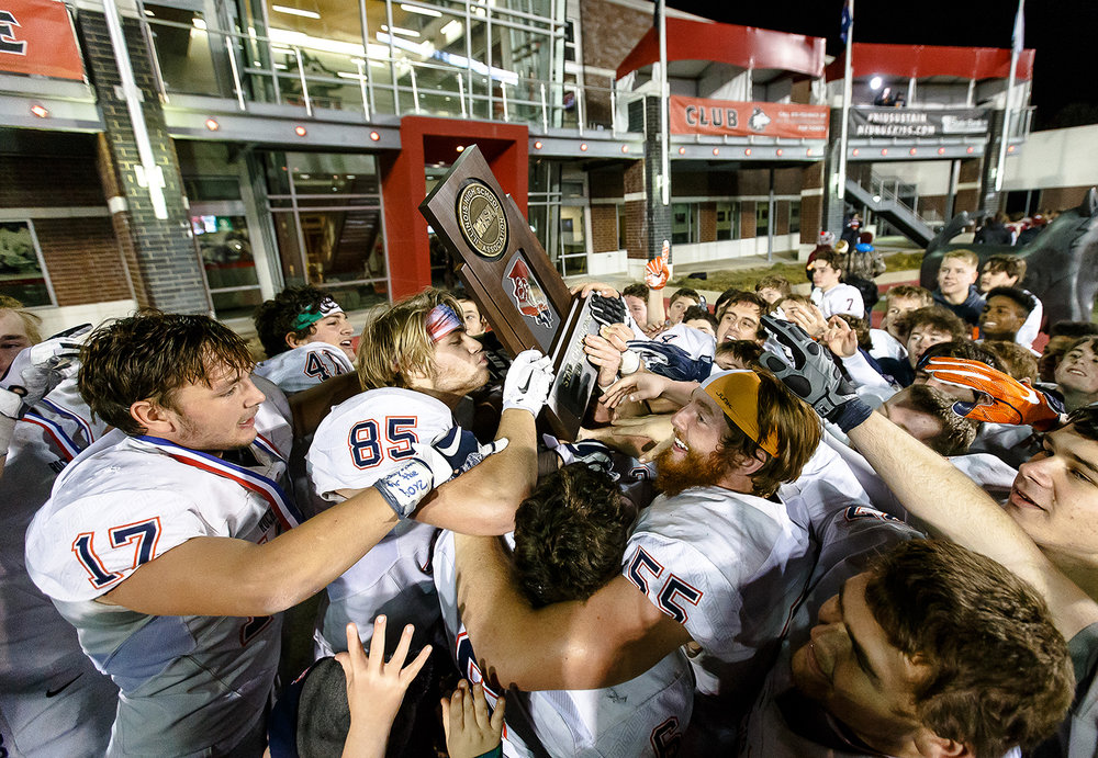 Rochester's Mike McNicholas (85) gets a kiss of the trophy as the Rockets celebrate their 24-21 victory over Morris in  the IHSA Class 4A State Championship at Huskie Stadium, Friday, Nov. 24, 2017, in Dekalb, Ill. [Justin L. Fowler/The State Journal-Register]