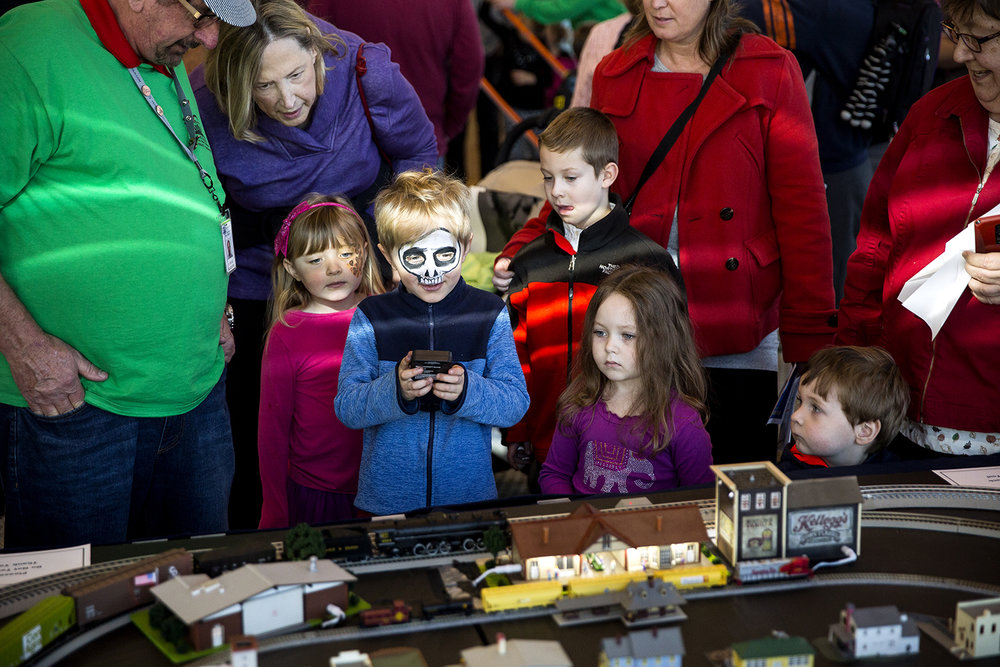Warren Jost, center, holds the controls to a model train display during the Fun Frosty Friday event at the Abraham Lincoln Presidential Library, Friday, Nov. 24, 2017, in Springfield, Ill. The trains belong to Chuck Blackburn, left, who is a volunteer at the presidential museum and also the Chatham Railroad Museum. The event included  a magician, face painting, games, balloon art, a life-sized Candy Land Adventure and visits with Santa Claus. [Rich Saal/The State Journal-Register]