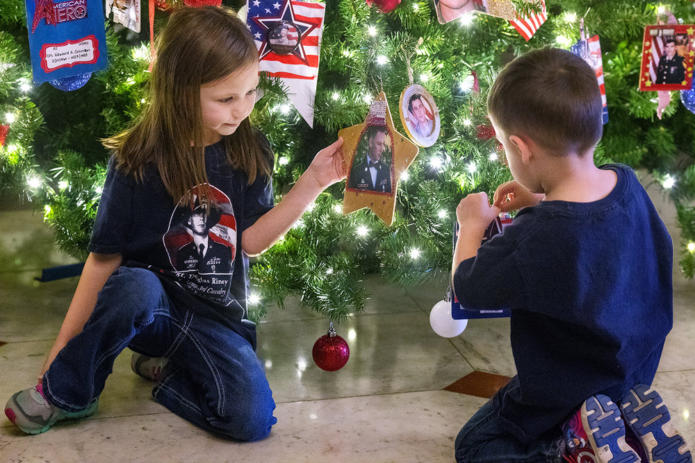Elea Riney holds the ornament of her father, Army Sgt. Douglas Riney, as her brother places another on the Fallen Heroes Tree of Honor in the Illinois State Capitol Rotunda during a dedication ceremony Monday, Nov. 27, 2017. Riney died October 19, 2016, of wounds received after encountering hostile enemy forces in Kabul, Afghanistan. He had been assigned to the Support Squadron, 3rd Cavalry Regiment, 1st Cavalry Division at Fort Hood, Texas, since December 2012. It was his second tour in Afghanistan. Gold Star family members and friends put up 155 ornaments on the tree during the ceremony. [Ted Schurter/The State Journal-Register]
