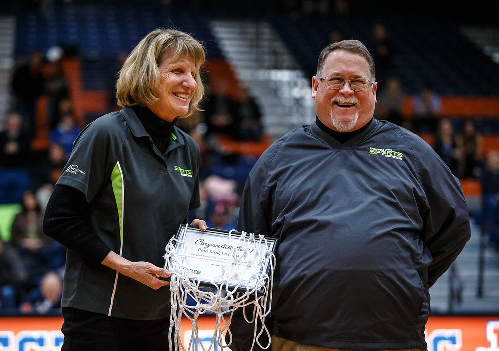 Dr. Diane Hillard-Sembell, left, honors trainer Pete Stoll, right, in conjunction with Stoll being named to the conjunction with Stoll being selected for the Illinois Basketball Coaches Association Hall of Fame Friend of Basketball prior to the Rockets taking on Sacred Heart-Griffin at the Rochester Athletic Center, Friday, Dec. 8, 2017, in Rochester, Ill. [Justin L. Fowler/The State Journal-Register]