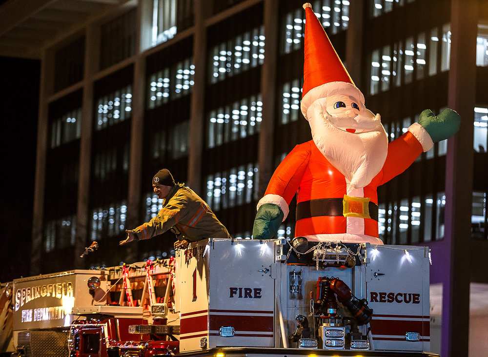 Springfield firefighter Bryce McCormick tosses out candy from the Truck 1 as he shares the ladder with a blow-up Santa Claus during the 2017 Springfield Jaycees Christmas Parade , Saturday, Dec. 9, 2017, in Springfield, Ill. [Justin L. Fowler/The State Journal-Register]