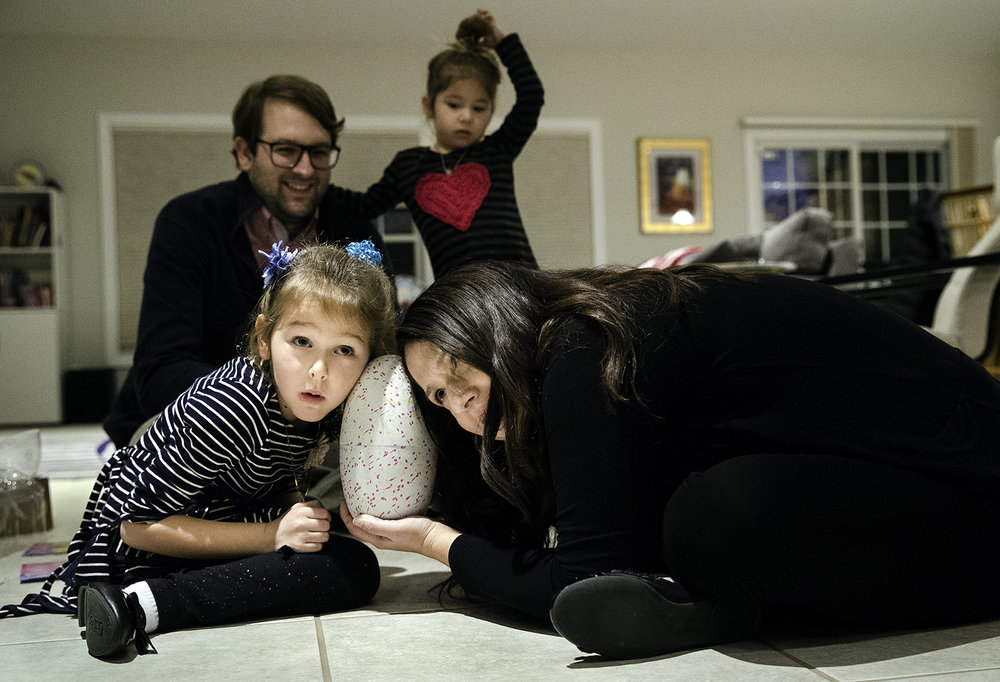 Elise Gross listens intently with her mom Amy after unwrapping the Hatchimal she received on the first night of the Jewish celebration of Hanukkah Tuesday, Dec. 12, 2017. The Hatchimal makes sounds, even in the egg, as it learns how to walk, talk, and play games after it hatches from its shell. Hanukkah, a festival of lights, is observed for eight nights and days. [Ted Schurter/The State Journal-Register]