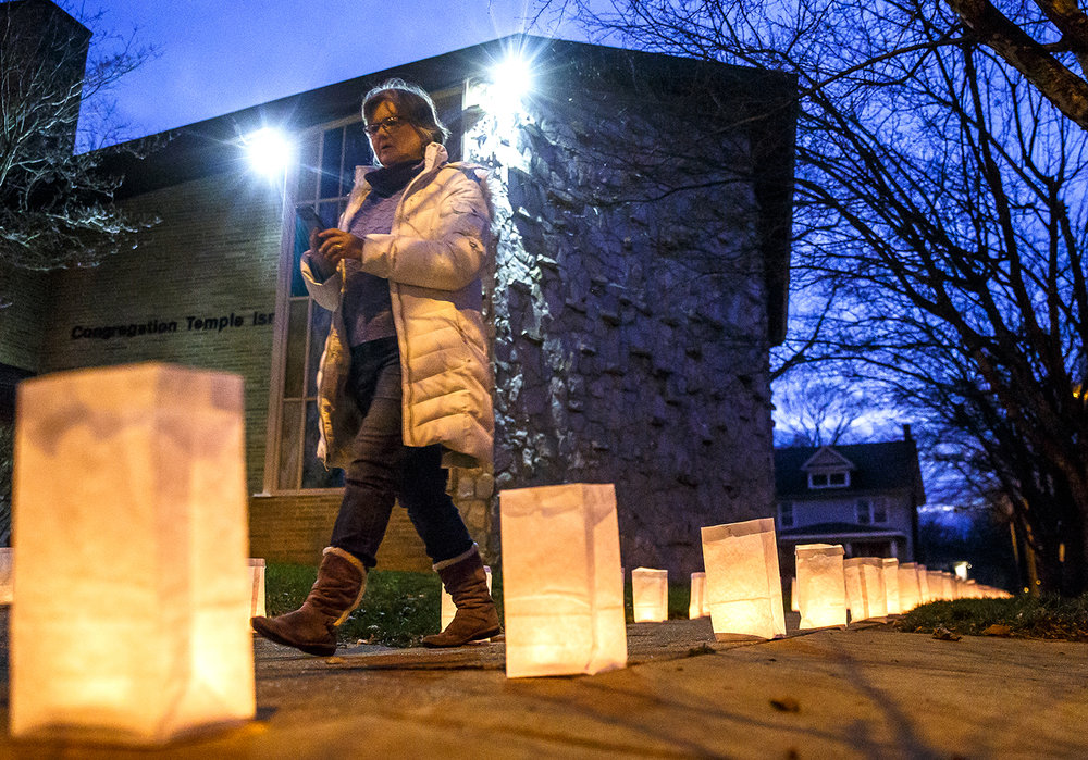 Valerie Klunick, a member of Douglas Avenue United Methodist Church, walks past Temple Israel as the synagogue and church, located next to each other on West Governor Street, are wrapped in over 1,500 luminaria celebrating the two congregations unity over the holidays, Thursday, Dec. 14, 2017, in Springfield, Ill. [Justin L. Fowler/The State Journal-Register]
