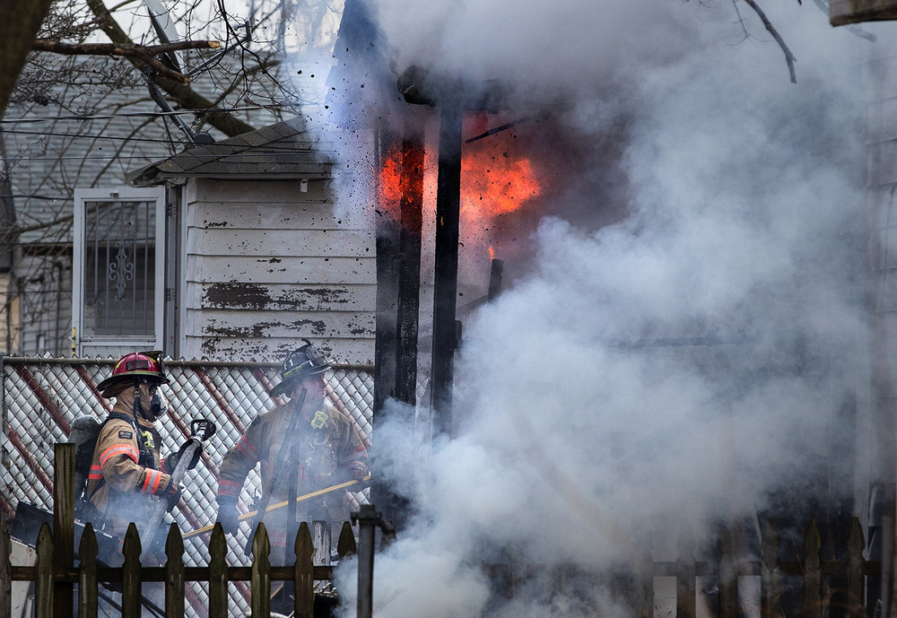 Flames and debris blow out of the back porch of a home at 1913 East Cedar St. as Springfield firefighters respond to a fire Thursday, Dec. 14, 2017. No one was injured in the fire. [Ted Schurter/The State Journal-Register]