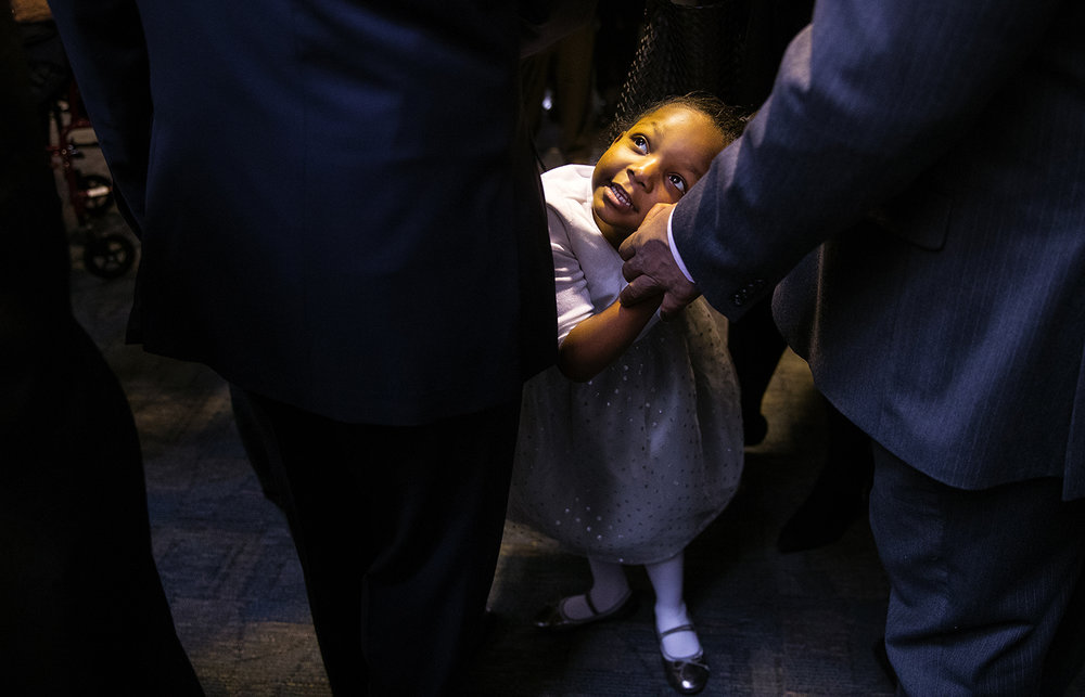 Jana Davis looks up at her father, Rep. William Davis, D-Hazel Crest, as they wait to enter Sangamon Auditorium for the inauguration of the 100th General Assembly at the University of Illinois Springfield Wednesday, Jan. 11. Ted Schurter/The State Journal-Register