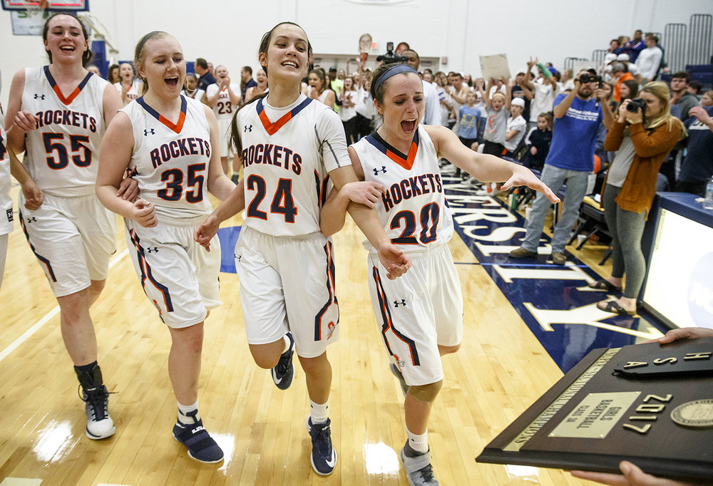 Rochester's Angela Perry, left, Madison Faulkner, Nicole Robinson and Aubrey Magro reach out for the title plaque after defeating Bethalto Civic Memorial 44-39 in the Class 3A Springfield Supersectional Feb. 27. Justin L. Fowler/The State Journal-Register