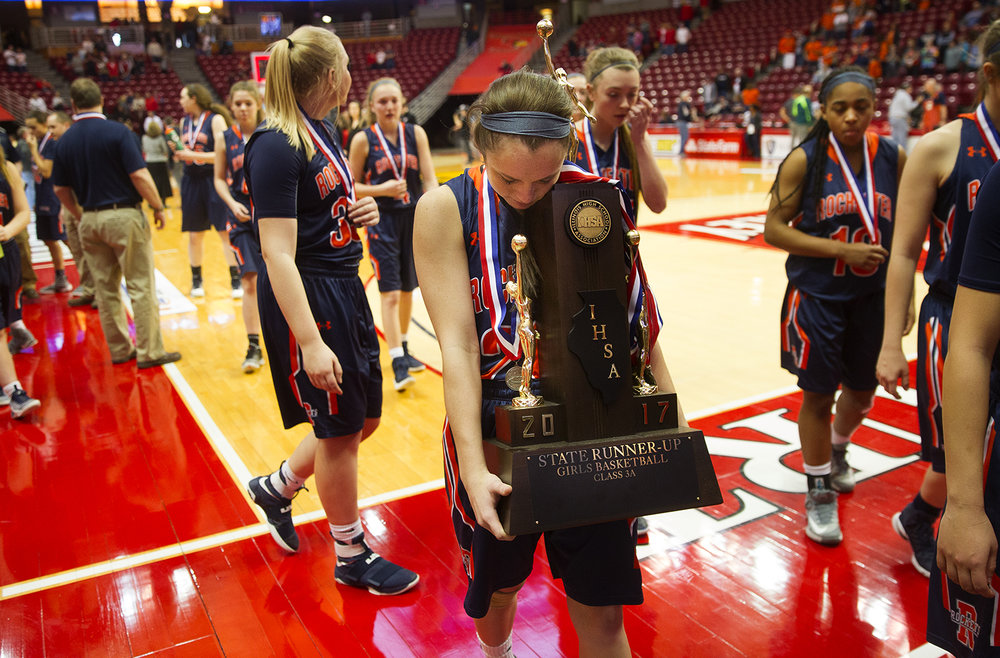 Rochester's Aubrey Magro carries the Runner-Up trophy off the court after the Rockets lost to Morton in the 2017 IHSA Girls Basketball Class 3A championship game at Redbird Arena in Normal March 3. Ted Schurter/The State Journal-Register