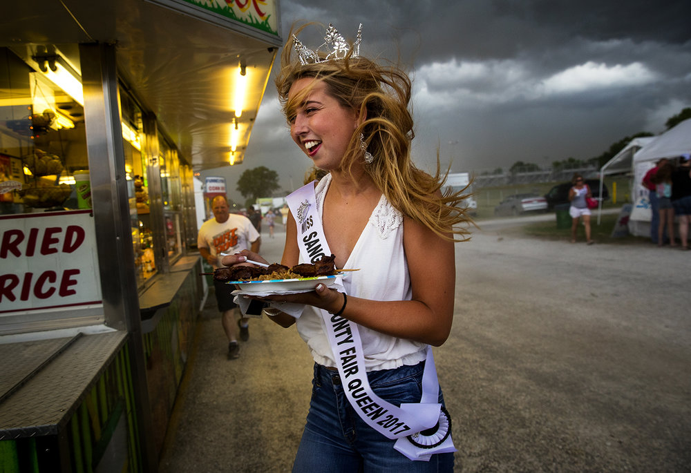 Sangamon County Fair Queen Alyssa McGarvy heads for shelter when a storm front suddenly blows across the Sangamon County Fairgrounds June 14, temporarily interrupting her dinner break. Ted Schurter/The State Journal-Register