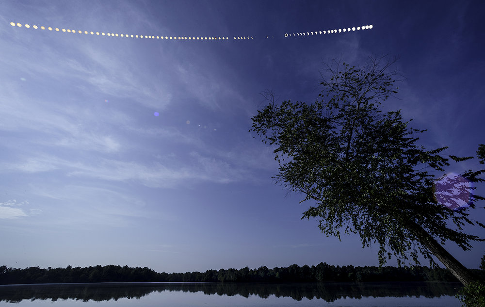 A composite image shows the path of the sun exposed every four minutes during the total solar eclipse over the Carbondale Reservoir Aug. 21. Gaps in the sequence are where clouds obscured the sun. Ted Schurter/The State Journal-Register