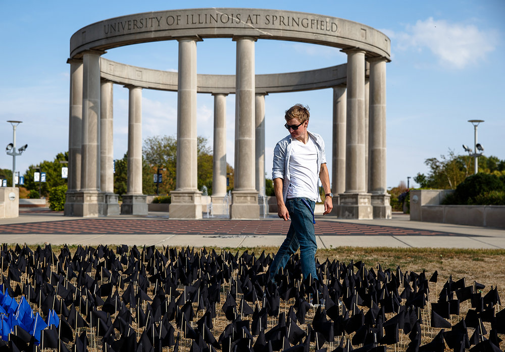 Brandon Klages, a junior legal studies major at the University of Illinois Springfield, walks through a display of 2,098 flags placed on the UIS Quad on International Wrongful Conviction Day, Oct. 2. Each of the flags represented men and women convicted of crimes they did not commit who had been exonerated since 1989 by the work of the Illinois Innocence Project. Justin L. Fowler/The State Journal-Register
