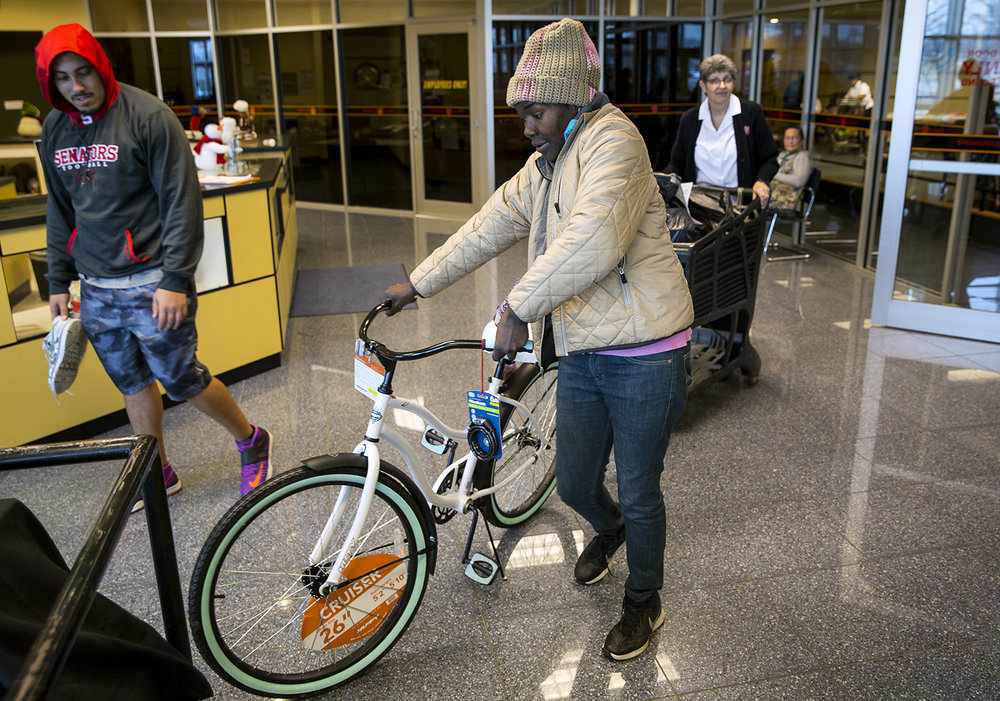 Bobbie White wheels a new bicycle toward her car Tuesday, Dec. 19, 2017 at The Salvation Army Clear Lake Corps and Community Center, 1600 E Clear Lake Ave. in Springfield, where they held their annual Angel Tree Christmas gift distribution. The bike is for White's daughter, Destinee, 13, whose previous bike had been stolen. This one came with a lock. According to the Salvation Army, 254 families this year were presented with toys and food through the program. [Rich Saal/The State Journal-Register]