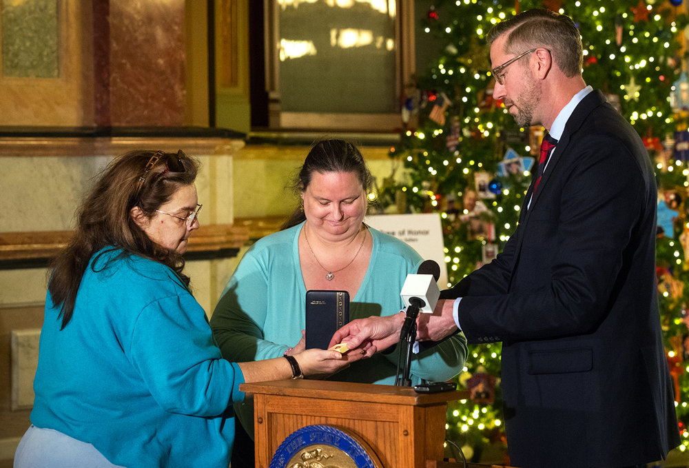 Illinois State Treasurer Michael Frerichs returns a collection of military medals, including the Purple Heart, a National Defense Medal, Vietnam Service Medal, a Combat Action Ribbon and a Presidential Unit Citation Ribbon earned by PFC Andrew Gust Richard to his nieces Jane, left, and Bertha Richard during a ceremony in the Illinois State Capitol Rotunda Tuesday, Dec. 19, 2017. [Ted Schurter/The State Journal-Register]