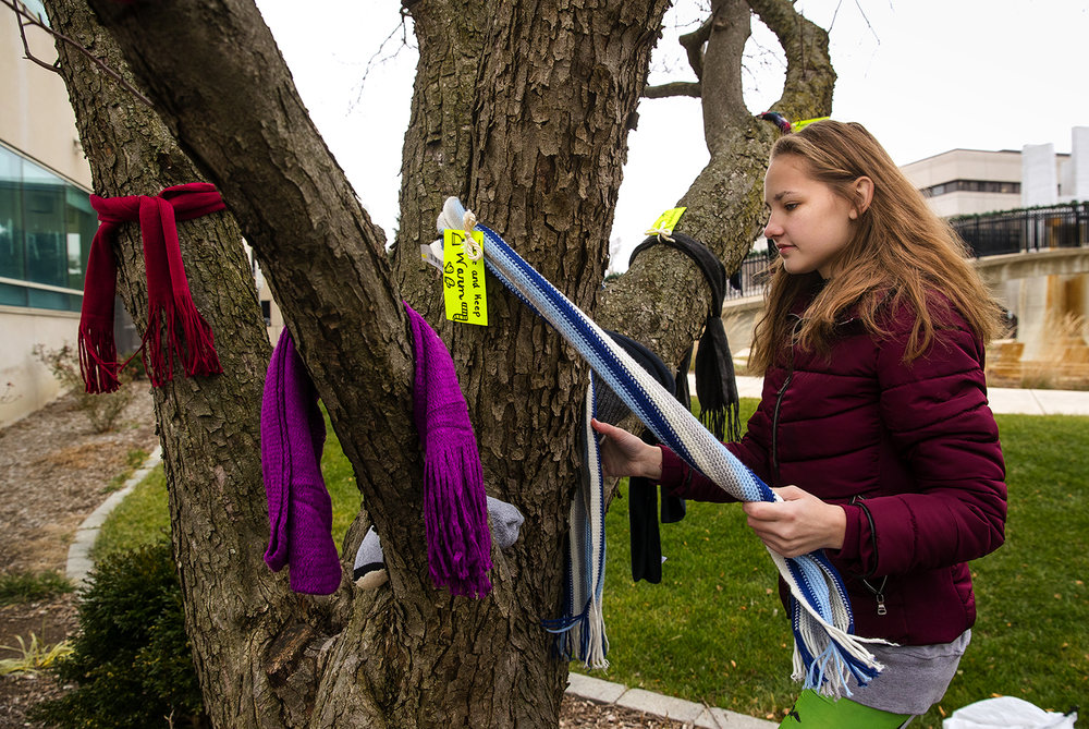 Carolyn Grenda ties a scarf around a tree Friday, Dec. 22, 2017. Grenda and six other students from the service club Helping Everyone Around Rochester, Taylorville and Springfield placed about 100 winter wear items including hats, gloves and scarves between the two municipal buildings downtown with an invitation for anyone that needs them to help themselves. [Ted Schurter/The State Journal-Register]