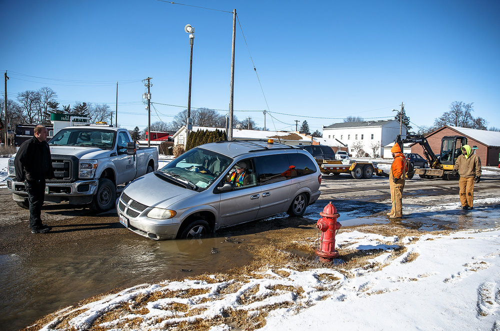 A motorist finds their vehicle stuck in the hole created from a broken water main and subsequent leak after driving around the heavy equipment setup to repair it at the intersection of West Street and East Hargrave Street, Friday, Jan. 5, 2018, in Athens, Ill. The city of Athens has shut down water service and issued a boil order until further notice. [Justin L. Fowler/The State Journal-Register]