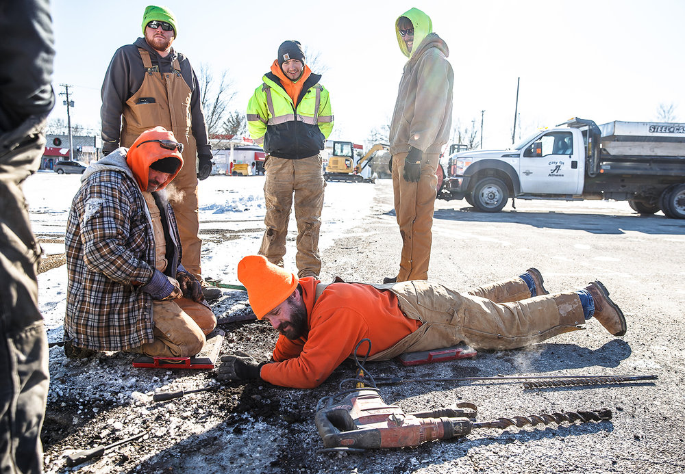 Dan Ingersoll, of Prairie State Plumbing and Heating, had to use a drill with an auger bit to get through the frozen ground as they try to get down to a valve to try and shut off the source of a water main break at the intersection of West Street and East Hargrave Street, Friday, Jan. 5, 2018, in Athens, Ill. The city of Athens has shut down water service and issued a boil order until further notice. [Justin L. Fowler/The State Journal-Register]