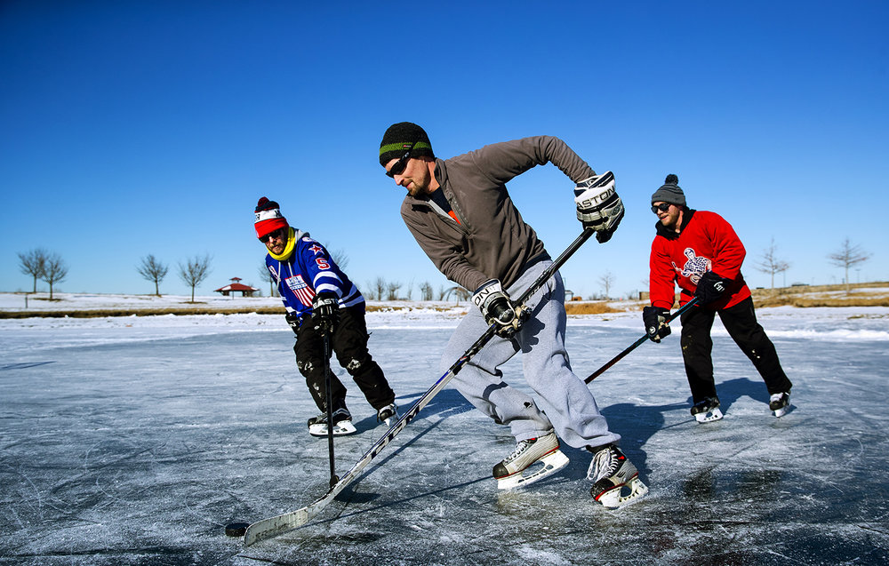 John Richardson, center guides the puck away from Derrick Brown, left, and Mike Sullivan as they play hockey on the frozen waters of the pond at Southwind Park Saturday, Jan. 6, 2017. Days of sub-freezing temperatures created a slab of ice well thicker than the four inches required for safe skating. [Ted Schurter/The State Journal-Register]