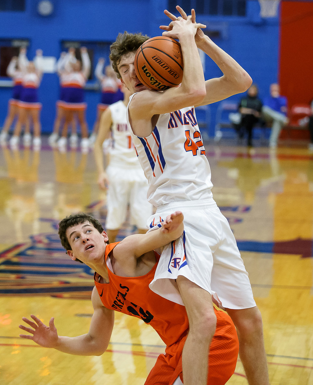 New Berlin's Connor Allen (22) fouls Riverton's Spencer Yoggerst (42) as he slides underneath him in the first half during the semifinals of the Boys Sangamon County Tournament at Lincoln Land Community College's Cass Gymnasium, Wednesday, Jan. 10, 2018, in Springfield, Ill. [Justin L. Fowler/The State Journal-Register]